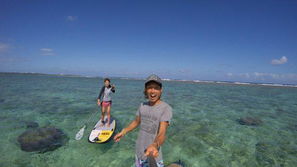サーフボードに乗る女性と自撮りする男性