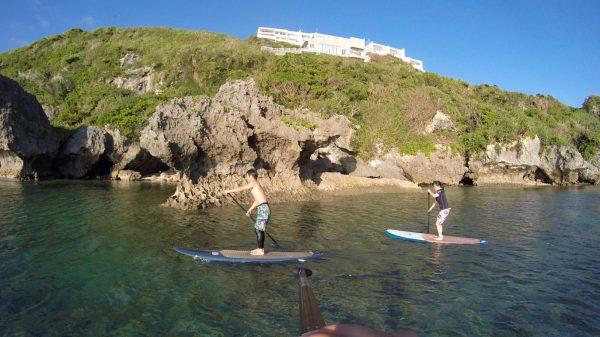 サーフボードに乗ってパドルを漕ぐ男女