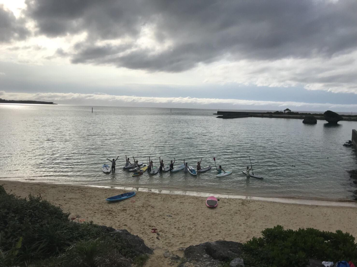曇り空の浜辺でsupをする人々